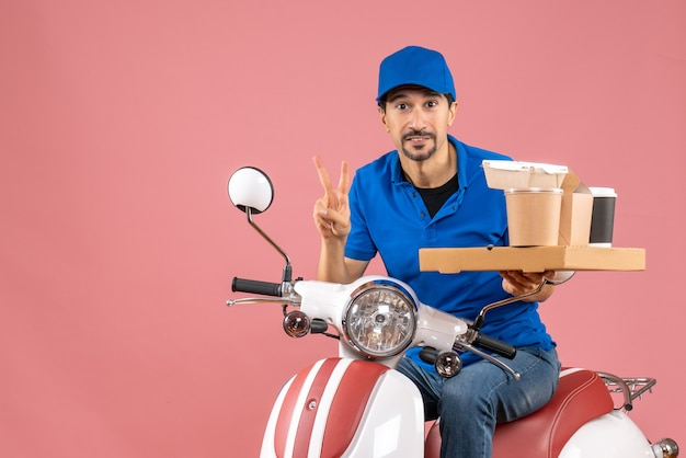 Vista dall'alto dell'uomo corriere felice che indossa un cappello seduto sullo scooter che fa il gesto di vittoria su sfondo color pesca pastello pastel