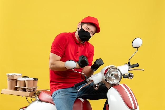 Vista superiore dell'uomo felice del corriere che indossa guanti rossi della camicetta e del cappello nella mascherina medica che trasporta l'ordine che si siede sul motorino
