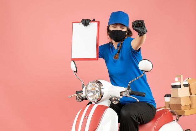 Vista dall'alto della donna corriere felice che indossa maschera medica e guanti seduta su uno scooter con in mano fogli di carta vuoti che consegnano ordini su sfondo color pesca pastello pastel