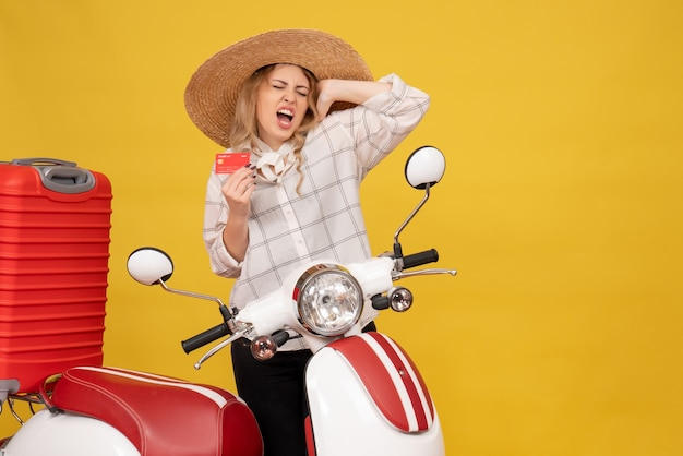 Top view of happy emotional young woman wearing hat collecting her luggage sitting on motorcycle and holding bank card