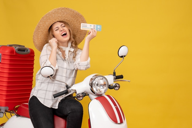 Top view of happy emotional young woman wearing hat and sitting on motorcycle and holding ticket on yellow