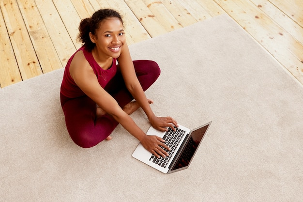 Top view of happy energetic young dark skinned woman with beaming smile sitting on carpet with generic portable computer, checking email after indoor training. sports and active lifestyle concept
