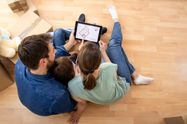 Top view of happy family choosing house interior design on tablet computer