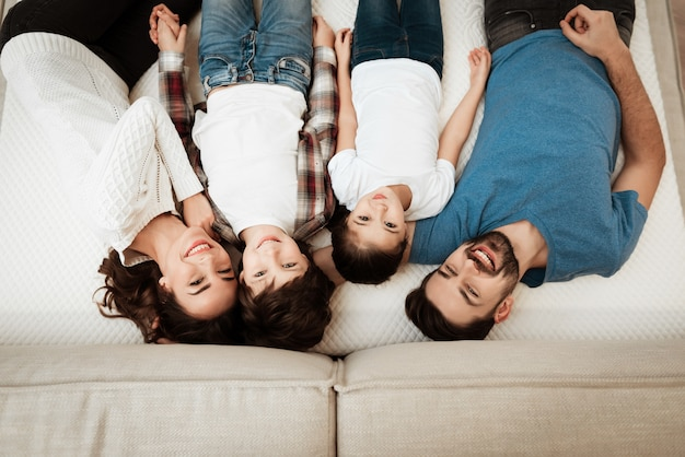 Top view of happy family relaxing on bed in store