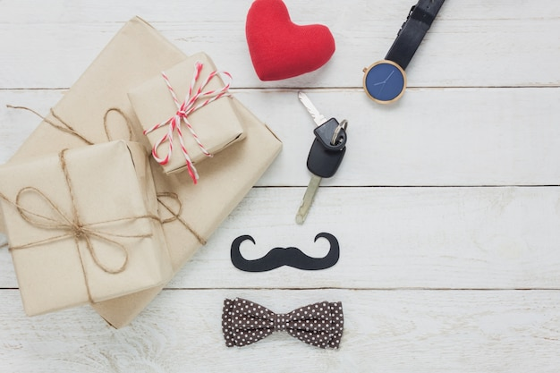Top view happy father day.accessories with red heart,mustache,vintage bow tie,present,key's car on rustic white wooden background.