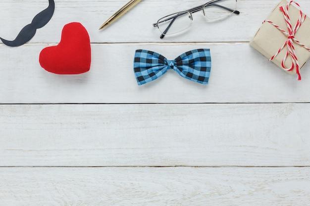 Vista superiore happy father day.accessories con cuore rosso, baffi, cravatta di arco vintage, presente, penna su sfondo bianco rustico di legno.