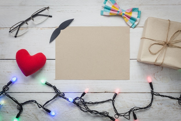 Vista superiore happy father day.blank carta per spazio libero testo su sfondo rustico di legno. accessori con, luci, regalo, baffi, fiocco d'arco vintage, occhiali, presente, cuore rosso.