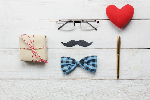 Top view happy father day.flat lay accessories with red heart,mustache,vintage bow tie,present,pen on rustic white wooden background.