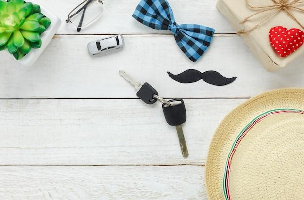 Vista superiore happy father day.key con auto per il regalo a padre.accessories con cuore rosso, baffi, cravatta d'arco vintage, presente, cappello e albero su sfondo rustico in legno bianco.