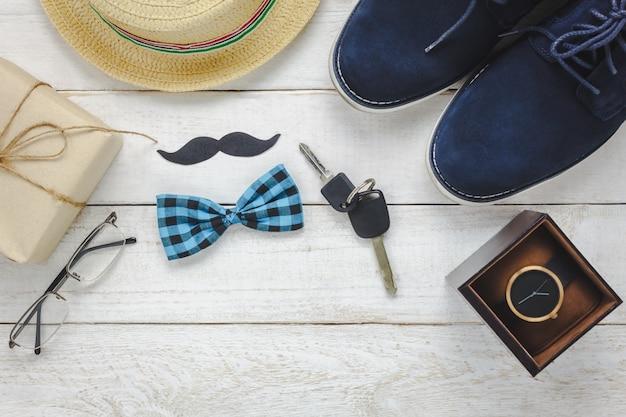 Vista superiore happy father day su sfondo rustico di legno. accessori con orologio, baffi, cravatta di arco vintage, penna, presente, chiave auto, scarpe e cappello.
