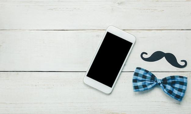 Вид сверху счастливый день отца. белый мобильный телефон на деревенском деревянном фоне. портрет отца - усы и винтажный галстук-бабочка.