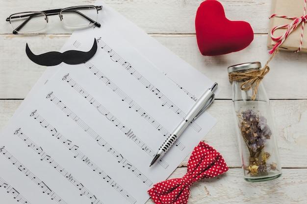 Vista superiore felice giorno del padre con musica concettuale.music note carta su sfondo rustico in legno.accessories con cuore rosso, regalo, baffi, fiocco di archi vintage, fiore secco in bottiglia e presente.