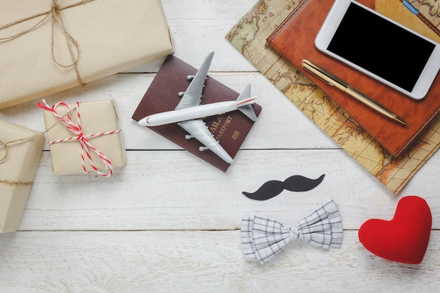 Top view happy father day with travel.airplane and passport on rustic wooden background.accessories with ,map,mustache,vintage bow tie,pen,present,red heart,white mobile phone and notebook.