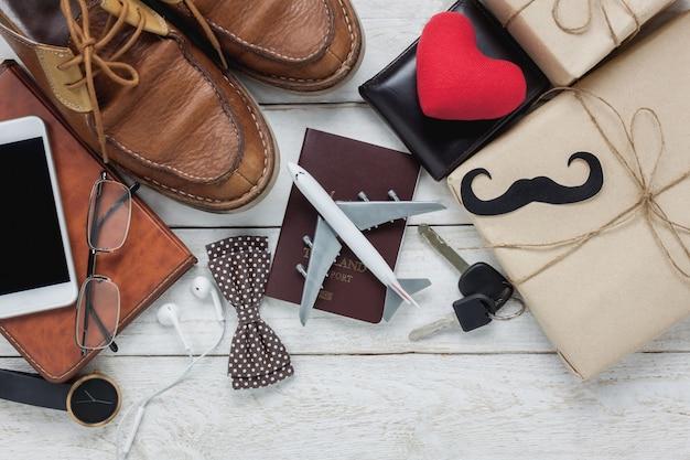 Вид сверху счастливый день отца с концепцией путешествия. самолет и паспорт на деревенском деревянном фоне. аксессуары с красным сердцем, усы, галстук-бабочка, ручка, подарок, белый мобильный телефон, обувь, наушники, часы и ноутбук.