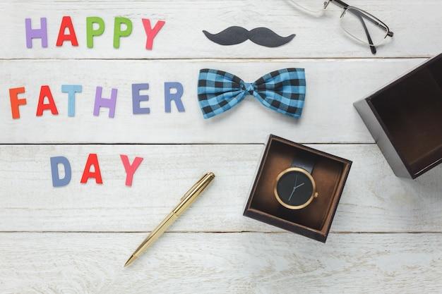 トップビューハッピー父の日コンセプト。木の背景に「お父さんのお誕生日」と言い添えてください。口ひげ、ヴィンテージのボウタイ、眼鏡、ギフトのためのプレゼントの時計付きのアクセサリー。