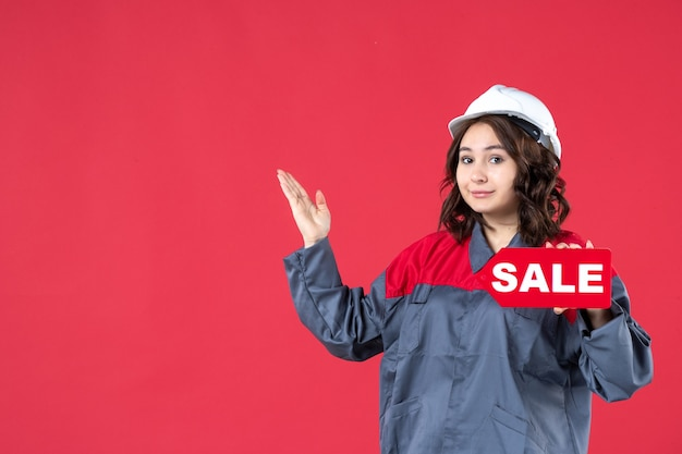 Vista dall'alto del costruttore femminile felice in uniforme che indossa un elmetto e mostra l'icona di vendita rivolta verso l'alto sul lato destro su sfondo rosso isolato