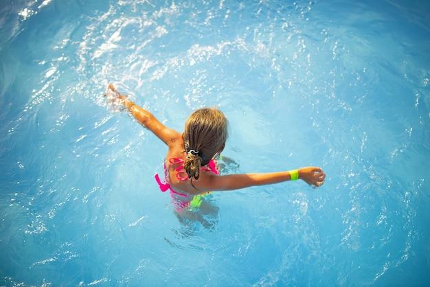 밝은 색 수영복에 상위 뷰 행복 한 어린 소녀는 맑은 따뜻한 수영장 물에서 수영 휴가 기간 동안 화창한 여름 날입니다. 가족 휴가 및 관광 개념.