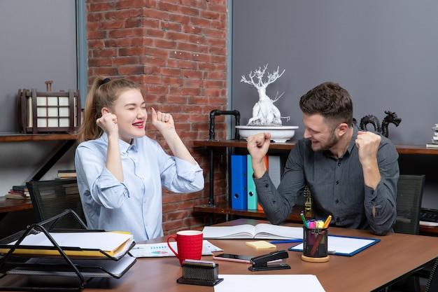 La vista dall'alto del team di gestione felice seduto al tavolo è arrivata alla negoziazione nella sala riunioni in ufficio
