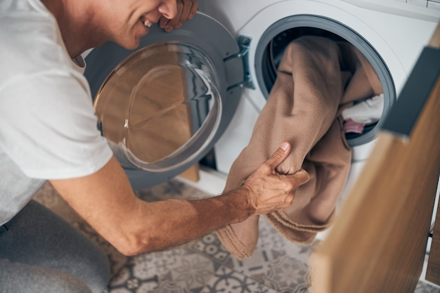 Top view of happy mature man doing home routine standing near the washing machine at home