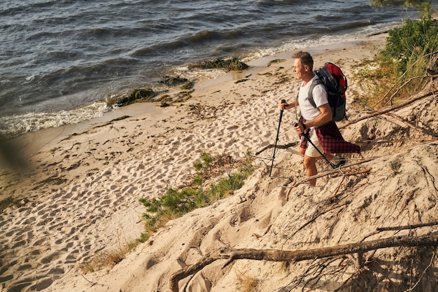Top view of happy mature man going nordic walking with trecking sticks near sea shore