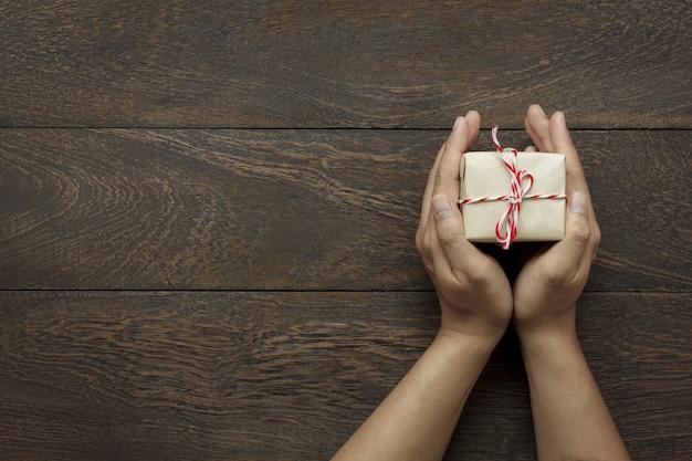 Вид сверху с новым годом фестиваля или день рождения и веселого рождества фона background.hands проведения little present.object на современном коричневом деревенском дереве на домашний офисный стол с копией пространства.