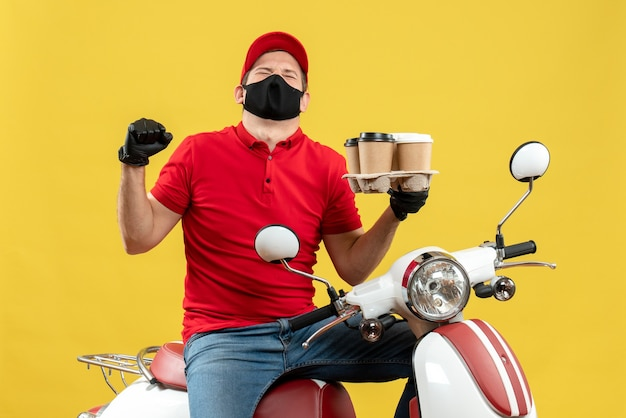 Top view of happy proud emotional delivery guy wearing uniform and hat gloves in medical mask sitting on scooter showing orders