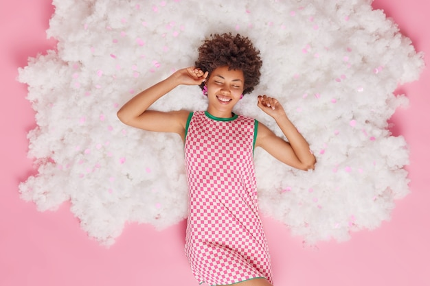 Top view of happy relaxed afro american woman smiles broadly keeps eyes closed