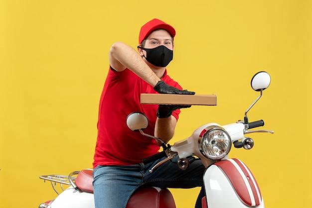 Vista superiore dell'uomo felice soddisfatto del corriere che indossa la camicetta rossa e guanti del cappello nella mascherina medica che si siede sullo scooter che mostra l'ordine