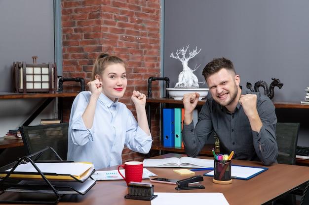 La vista dall'alto del team di gestione felice e soddisfatto seduto al tavolo è arrivata alla negoziazione nella sala riunioni in ufficio