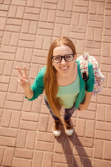 Top view of happy smiling woman in glasses showing two fingers