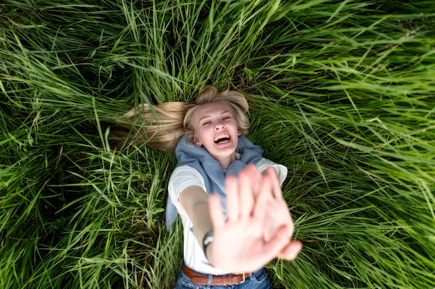 Top view of happy woman posing in grass