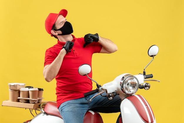 Vista superiore del giovane adulto felice che indossa guanti rossi della camicetta e del cappello nella mascherina medica che trasporta l'ordine che si siede sullo scooter che indica se stesso su fondo giallo