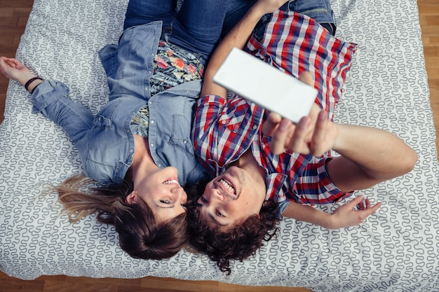 Top view of happy young couple in love taking a selfie with smartphone lying over a bed. leisure time at home concept.