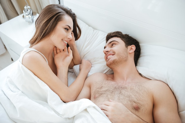 Top view of happy young couple lying and smiling in bed together