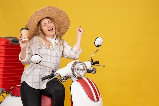 Top view of happy young woman wearing hat and sitting on motorcycle and holding coffee enjoying her succeess