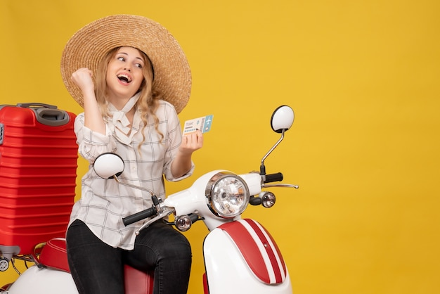 Top view of happy young woman wearing hat and sitting on motorcycle and holding ticket on yellow