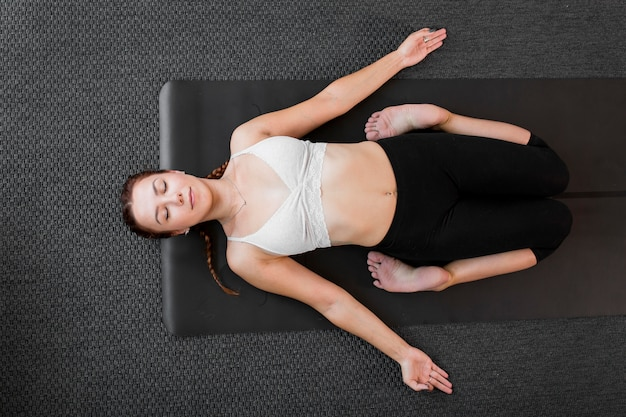 Top view hard position practicing yoga at home concept