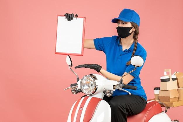 Vista dall'alto della laboriosa ragazza del corriere che indossa maschera medica e guanti seduta su uno scooter con in mano un foglio di carta vuoto che consegna ordini su sfondo color pesca pastello