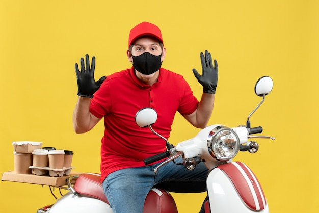 Top view of hardworking young adult wearing red blouse and hat gloves in medical mask delivering order sitting on scooter on yellow background