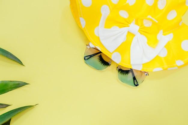 Шляпа и солнечные очки взгляд сверху на желтой предпосылке с солнечным светом и тенью листьев кокоса.