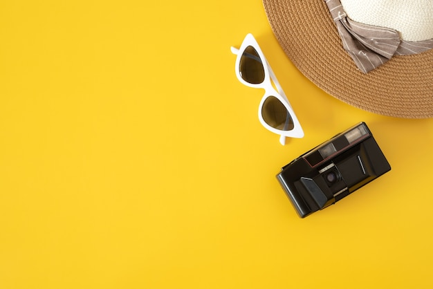 Top view of hat camera and sunglasses with colored background world tourism day