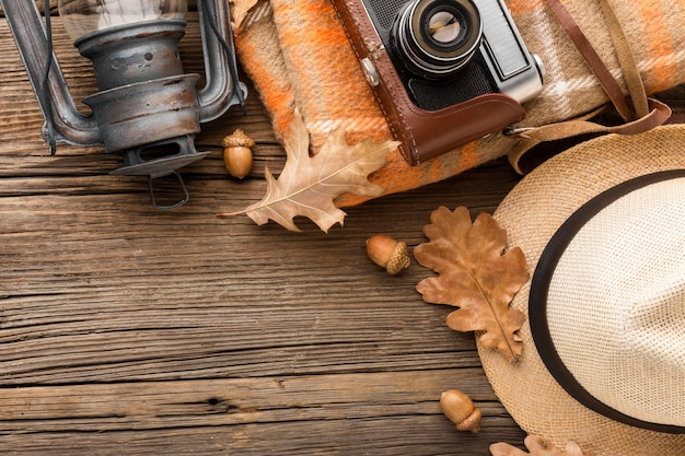 Top view of hat and camera with autumn leaves