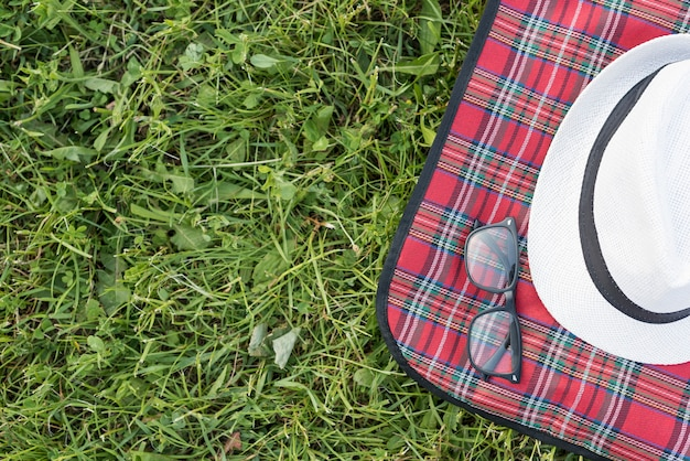Top view hat and glasses on picnic blanket