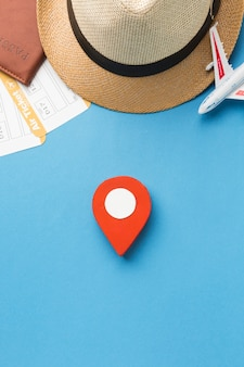 Top view of hat and travel essentials with pinpoint