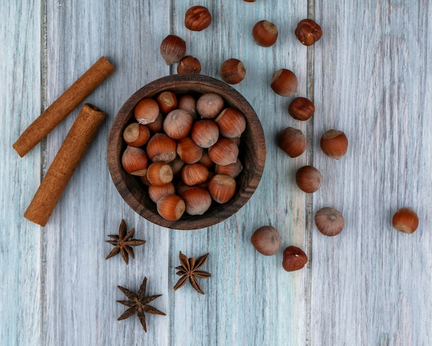 Top view hazelnut in a bowl with cinnamon on a gray background