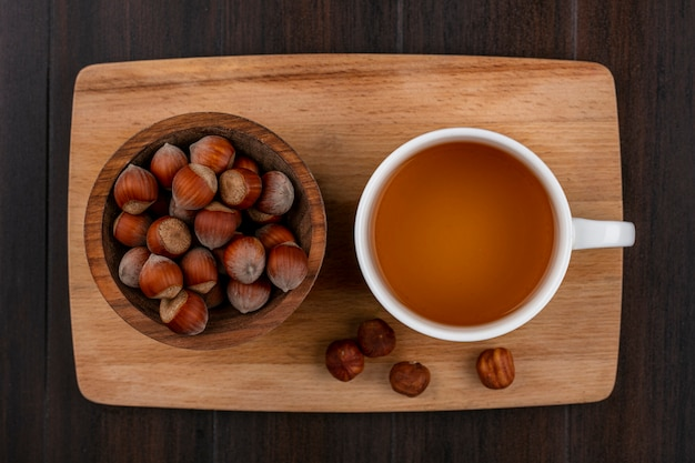Top view of hazelnut in a bowl with a cup of tea on a blackboard on a wooden surface