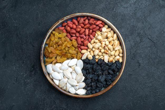 ダークグレーの表面にあるヘーゼルナッツ、レーズン、その他のナッツの上面図ナッツスナックドライフルーツの写真