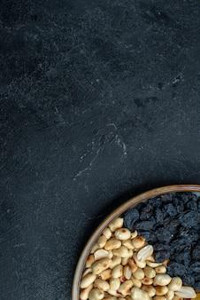 ダークグレーの背景にあるヘーゼルナッツ、レーズン、その他のナッツの上面図ナッツスナックドライフルーツの写真