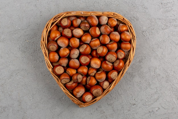 Top view hazelnuts inside basket on the grey desk