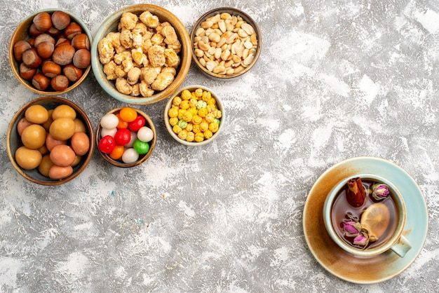 Top view of hazelnuts and peanuts with candies and cup of tea on white surface